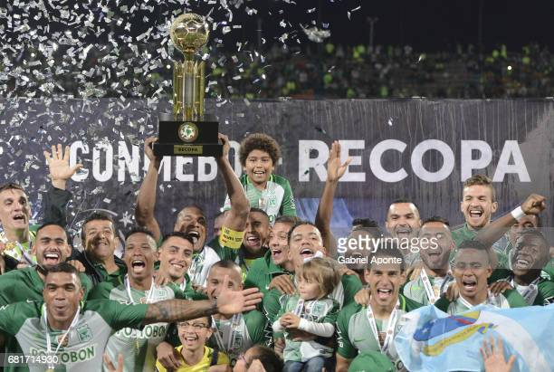Alexis Henriquez of Nacional lifts the trophy to celebrate with teammates after winning a match between Atletico Nacional and Chapecoense as part of...