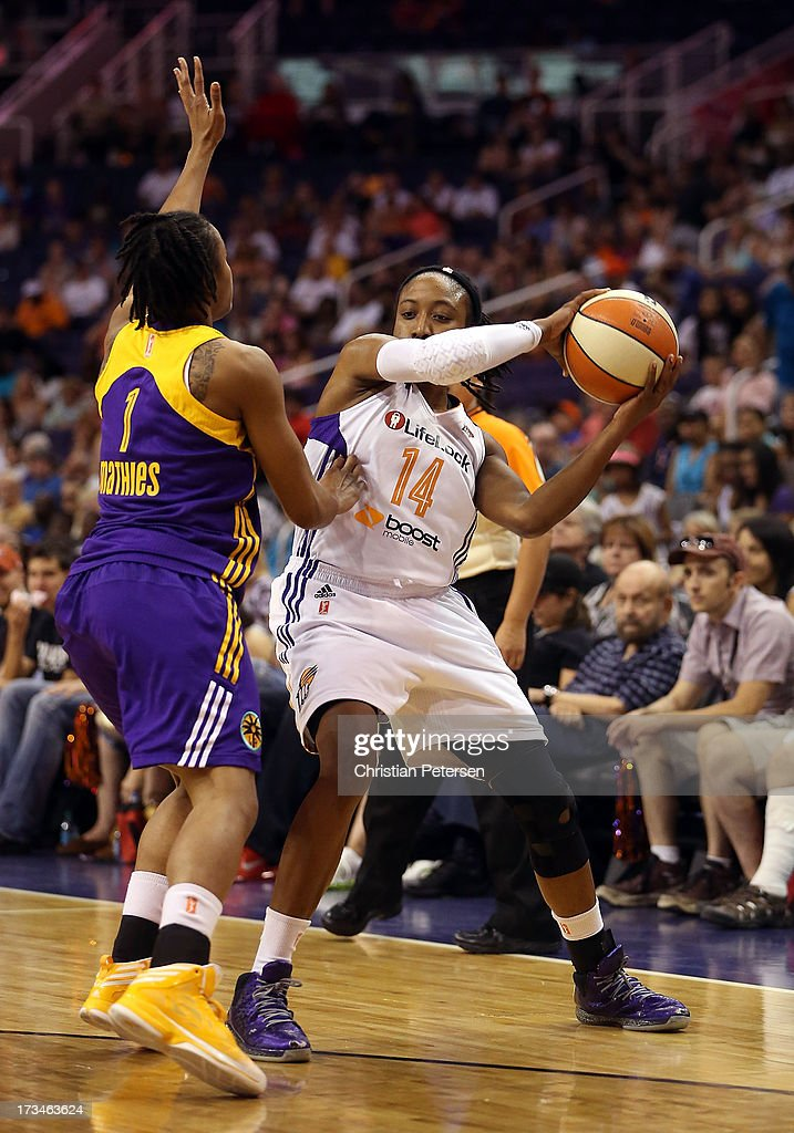 Alexis Hornbuckle #14 of the Phoenix Mercury looks to pass under pressure from A'dia Mathies #1 of the Los Angeles Sparks during the WNBA game at US Airways Center on July 14, 2013 in Phoenix, Arizona.