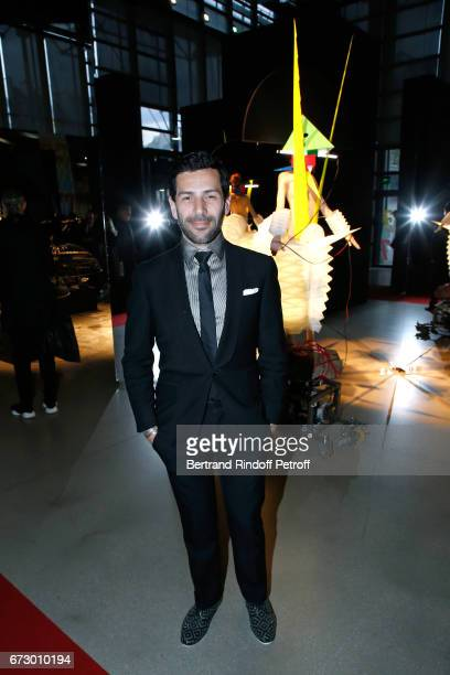 Alexis Mabill poses in front the works of JeanPaul Goude during the 'Societe des Amis du Musee d'Art Moderne du Centre Pompidou' Dinner Party Held at...