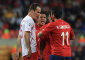 Alexis Sanchez and Mark Gonzalez of Chile hold back Gary Medel as Steve von Bergen of Switzerland looks on during the 2010 FIFA World Cup South...
