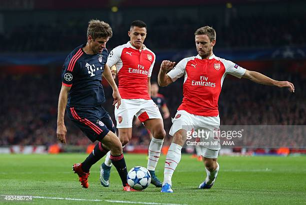 Alexis Sanchez and Nacho Monreal of Arsenal try to stop Thomas Muller of Bayern Munich during the UEFA Champions League match between Arsenal and...