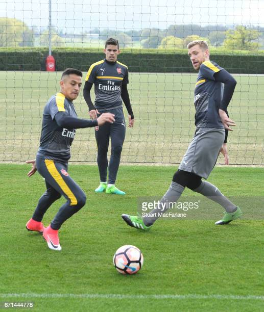 Alexis Sanchez and Per Mertesacker of Arsenal during a training session at London Colney on April 22 2017 in St Albans England