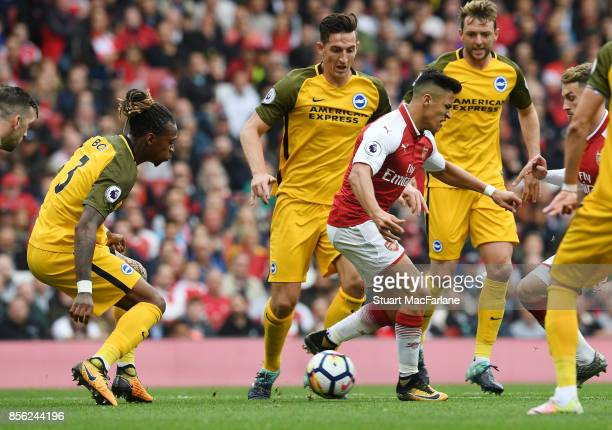 Alexis Sanchez backheels the ball past Brighton defender Gaetan Bong to set up Alex Iwobi to score the 2nd Arsenal goal during the Premier League...