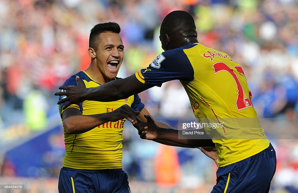 Alexis Sanchez celebrates scoring a goal for Arsenal with Yaya Sanogo during the Barclays Premier League match between Leicester City and Arsenal at The King Power Stadium on August 31, 2014 in Leicester, England.