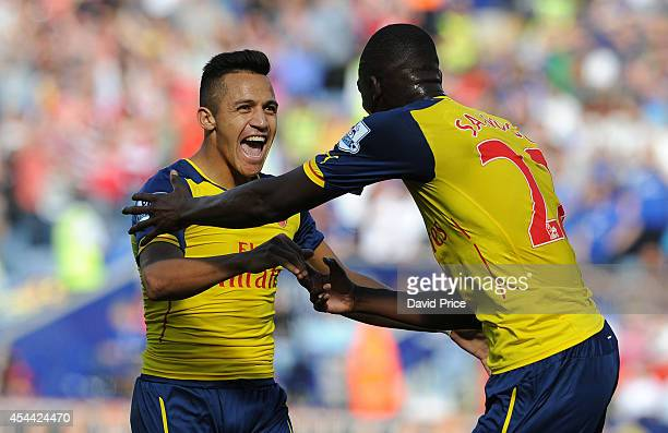 Alexis Sanchez celebrates scoring a goal for Arsenal with Yaya Sanogo during the Barclays Premier League match between Leicester City and Arsenal at...