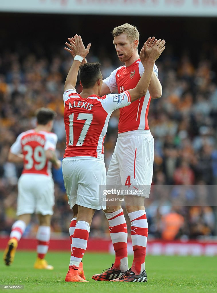 Alexis Sanchez celebrates scoring Arsenal's 1st goal with Per Mertesacker during the match between Arsenal and Hull City in the Barclays Premier League at Emirates Stadium on October 18, 2014 in London, England.