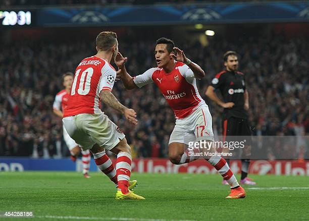 Alexis Sanchez celebrates scoring Arsenal's goal with Jack Wilshere during the UEFA Champions League Qualifier 2nd leg match between Arsenal and...
