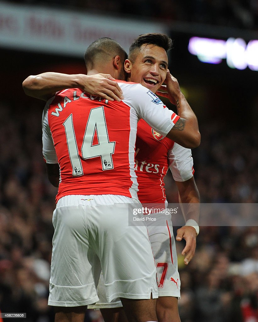 Alexis Sanchez celebrates scoring his 2nd goal Arsenal's 3rd with Theo Walcott during the match between Arsenal and Burnley in the Barclays Premier League at Emirates Stadium on November 1, 2014 in London, England.
