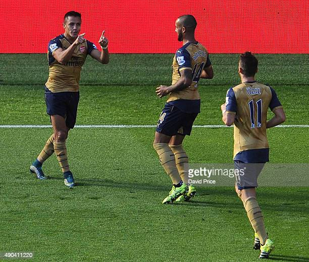 Alexis Sanchez celebrates scoring his 2nd goal Arsenal's 3rd with Theo Walcott and Mesut Ozil during the Barclays Premier League match between...