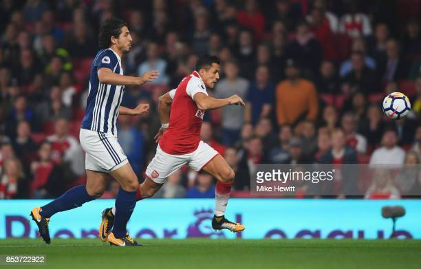 Alexis Sanchez of Arsenal and Ahmed ElSayed Hegazi of West Bromwich Albion chase the ball during the Premier League match between Arsenal and West...