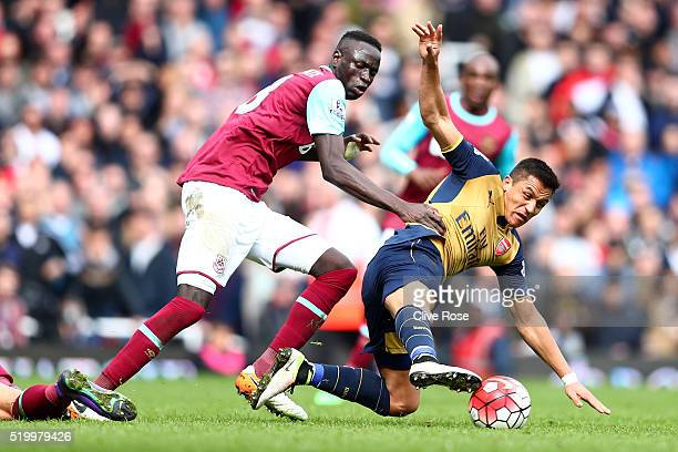 Alexis Sanchez of Arsenal and Cheikhou Kouyate of West Ham United compete for the ball during the Barclays Premier League match between West Ham...