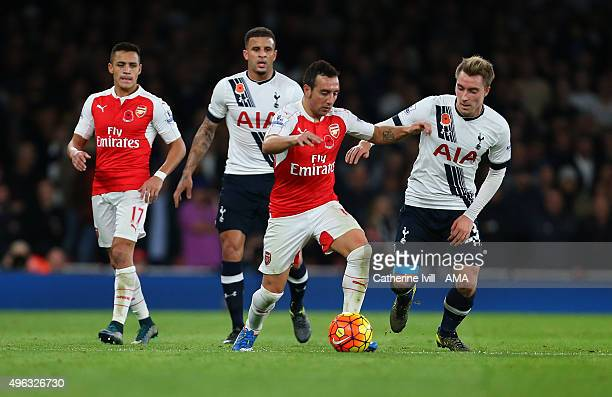 Alexis Sanchez of Arsenal and Kyle Walker of Tottenham Hotspur look on as Santi Cazorla of Arsenal battles with Christian Eriksen of Tottenham...