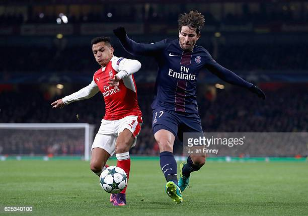 Alexis Sanchez of Arsenal and Maxwell of PSG battle for possession during the UEFA Champions League Group A match between Arsenal FC and Paris...