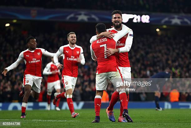 Alexis Sanchez of Arsenal and Olivier Giroud of Arsenal celebrate after their side score their second goal through a own goal by Marco Verratti of...