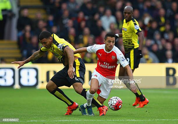 Alexis Sanchez of Arsenal and Troy Deeney of Watford compete for the ball during the Barclays Premier League match between Watford and Arsenal at...