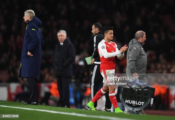 Alexis Sanchez of Arsenal apluds the crowd as he walks past Arsene Wenger Manager of Arsenal as he is substituted during the UEFA Champions League...