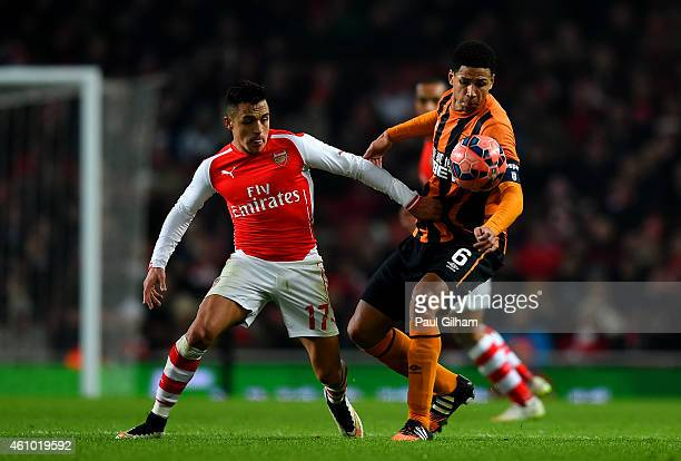Alexis Sanchez of Arsenal battles for the ball with Curtis Davies of Hull City during the FA Cup Third Round match between Arsenal and Hull City at...