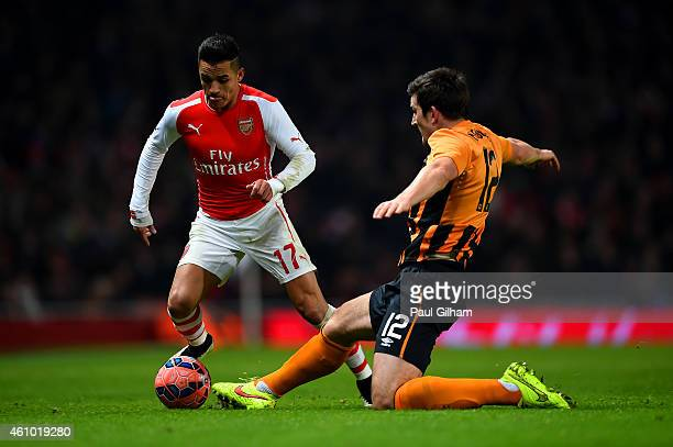 Alexis Sanchez of Arsenal battles for the ball with Harry Maguire of Hull City during the FA Cup Third Round match between Arsenal and Hull City at...