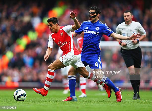 Alexis Sanchez of Arsenal beats Cesc Fabregas of Chelsea during the Barclays Premier League match between Arsenal and Chelsea at Emirates Stadium on...