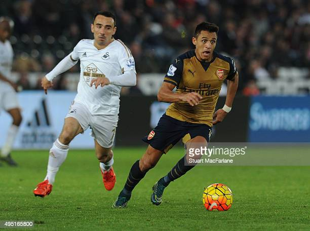 Alexis Sanchez of Arsenal breaks past Leon Britton of Swansea during the Barclays Premier League match between Swansea City and Arsenal at Liberty...