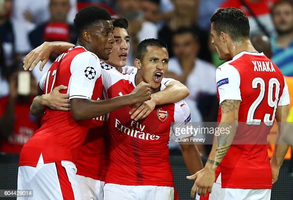 Alexis Sanchez of Arsenal celebrates scoring his sides first goal with team mates during the UEFA Champions League Group A match between Paris...