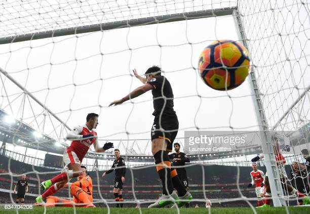 Alexis Sanchez of Arsenal celebrates scoring the opening goal while Harry Maguire of Hull City appeals the hand ball during the Premier League match...