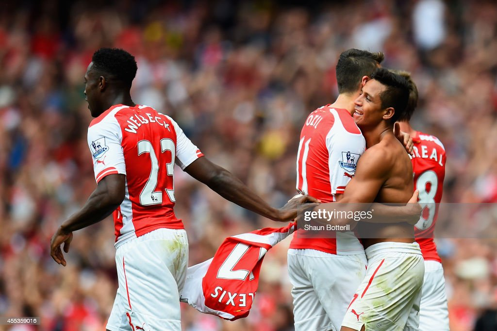 Alexis Sanchez of Arsenal celebrates scoring their second goal with Mesut Oezil and Danny Welbeck of Arsenal during the Barclays Premier League match between Arsenal and Manchester City at Emirates Stadium on September 13, 2014 in London, England.