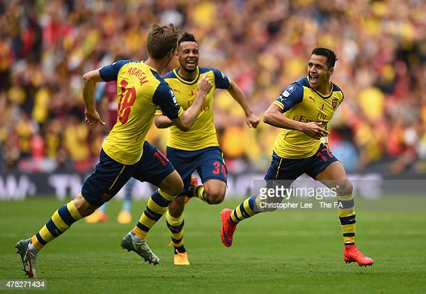 Alexis Sanchez of Arsenal celebrates with his teammates Nacho Monreal and Francis Coquelin after scoring their second goal during the FA Cup Final...