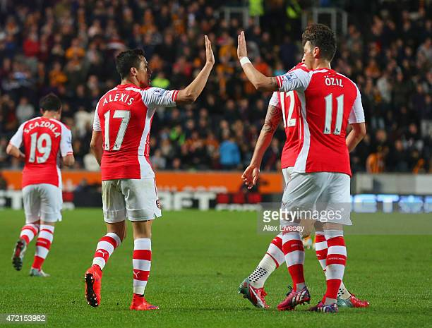 Alexis Sanchez of Arsenal celebrates with Mesut Oezil as he scores their third goal during the Barclays Premier League match between Hull City and...