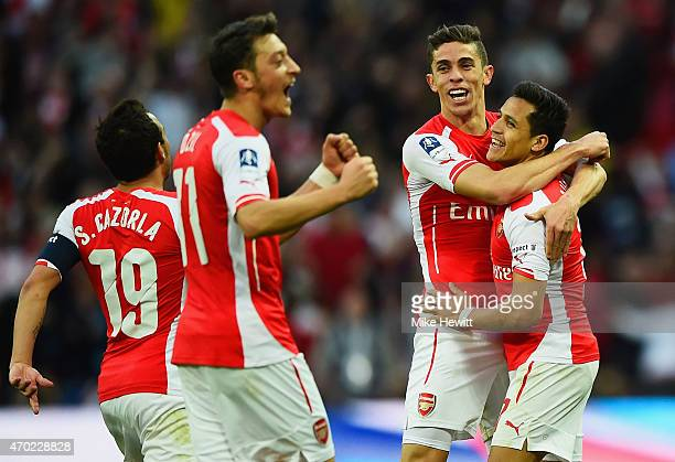 Alexis Sanchez of Arsenal celebrates with Santi Cazorla Mesut Oezil and Gabriel as he scores their second goal during the FA Cup Semi Final between...