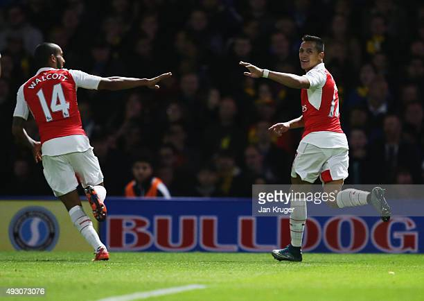 Alexis Sanchez of Arsenal celebrates with team mate Theo Walcott as he scores their first goal during the Barclays Premier League match between...