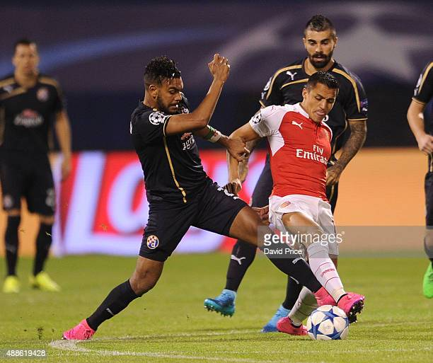 Alexis Sanchez of Arsenal challenges El Arabi Hilal Soudani of Dinamo during the match between GNK Dinamo Zagreb and Arsenal on September 16 2015 in...