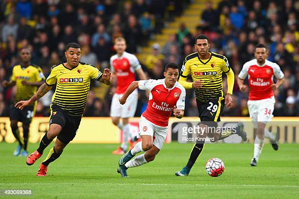 Alexis Sanchez of Arsenal competes against Troy Deeney and Etienne Capoue of Watford during the Barclays Premier League match between Watford and...