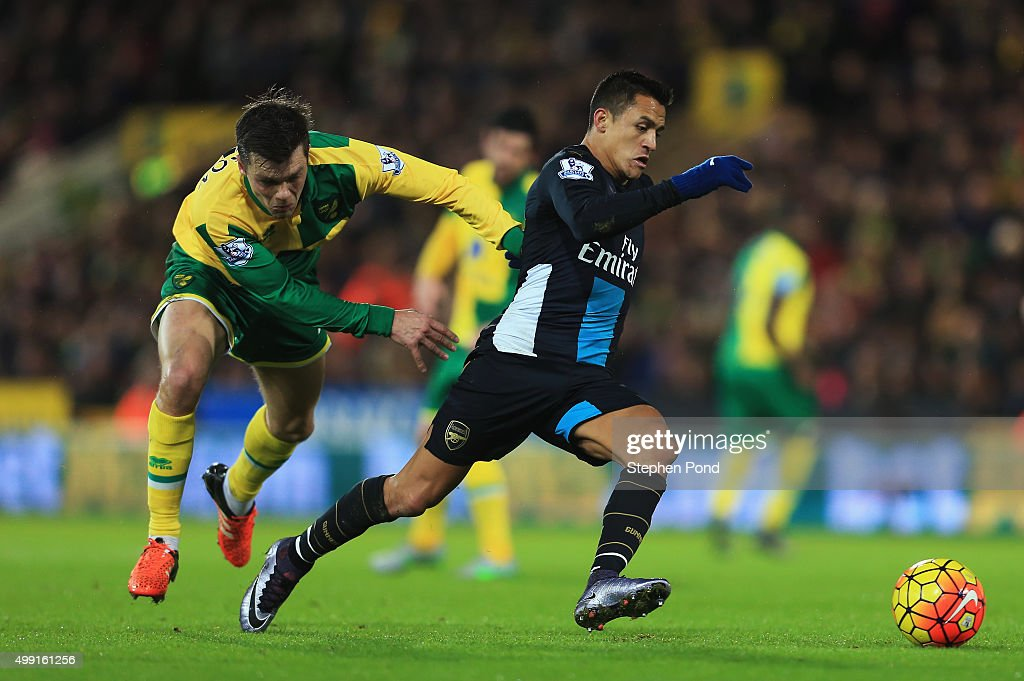 Alexis Sanchez of Arsenal evades Jonathan Howson of Norwich City during the Barclays Premier League match between Norwich City and Arsenal at Carrow Road on November 29, 2015 in Norwich, England.