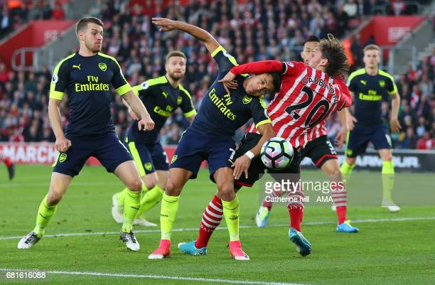 Alexis Sanchez of Arsenal gets caught up with Manolo Gabbiadini of Southampton during the Premier League match between Southampton and Arsenal at St...