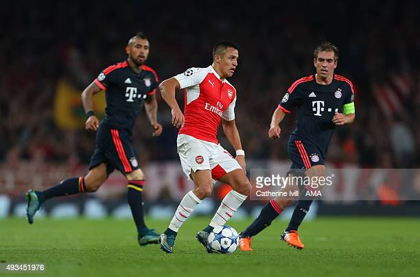 Alexis Sanchez of Arsenal gets past Arturo Vidal and Philipp Lahm of Bayern Munich during the UEFA Champions League match between Arsenal and Bayern...