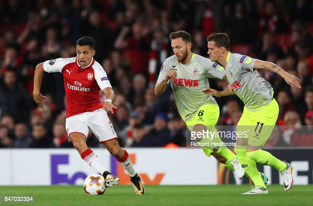 Alexis Sanchez of Arsenal goes past Marco Hoger of FC Koeln and Simon Zoller of FC Koeln during the UEFA Europa League group H match between Arsenal...