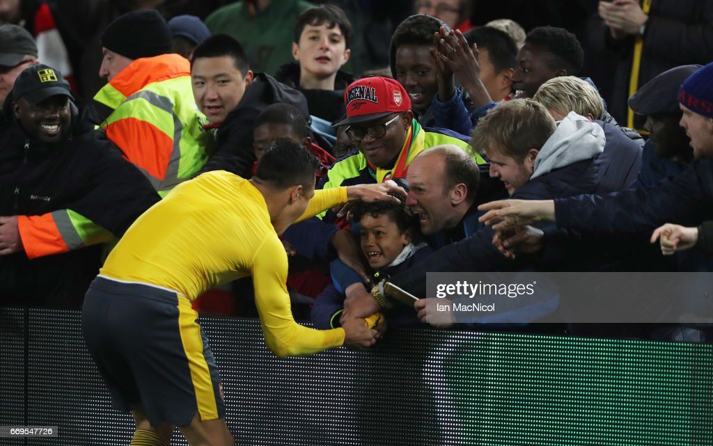 Alexis Sanchez of Arsenal hands his shirt to a young fan after the Premier League match between Middlesbrough and Arsenal at Riverside Stadium on April 17, 2017 in Middlesbrough, England.