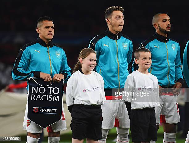 Alexis Sanchez of Arsenal holds a 'No To Racism' pennant as he stands with team mates Mesut Oezil and Theo Walcott and player escorts during the UEFA...