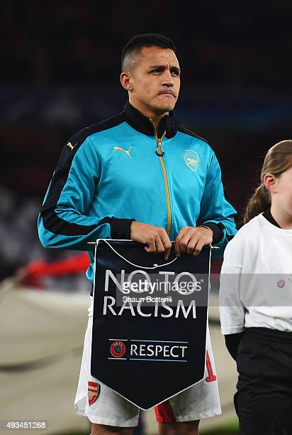 Alexis Sanchez of Arsenal holds a 'No To Racism' pennant prior to the UEFA Champions League Group F match between Arsenal FC and FC Bayern Munchen at...