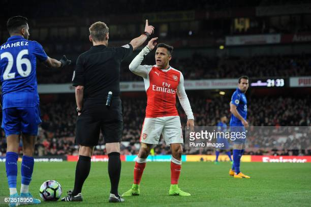 Alexis Sanchez of Arsenal is booked by referee Mike Jones during the Premier League match between Arsenal and Leicester City at Emirates Stadium on...