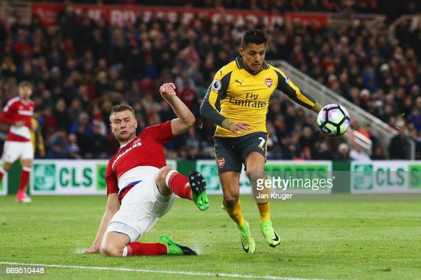 Alexis Sanchez of Arsenal is challenged by Ben Gibson of Middlesbrough during the Premier League match between Middlesbrough and Arsenal at Riverside...