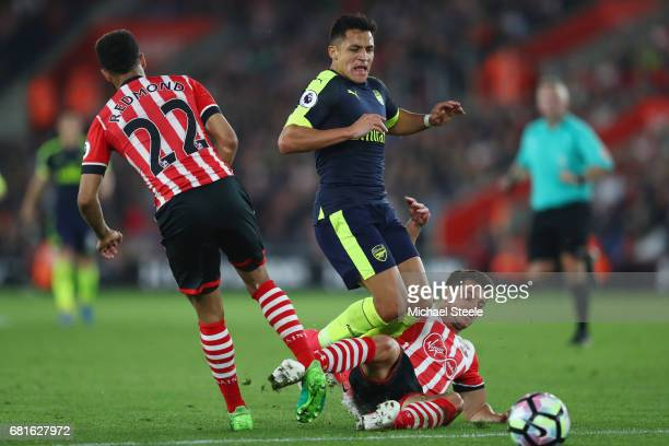 Alexis Sanchez of Arsenal is challenged by Cedric Soares of Southampton during the Premier League match between Southampton and Arsenal at St Mary's...