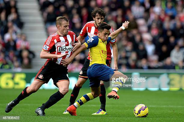 Alexis Sanchez of Arsenal is challenged by Lee Cattermole and Will Buckley of Sunderland during the Barclays Premier League match between Sunderland...