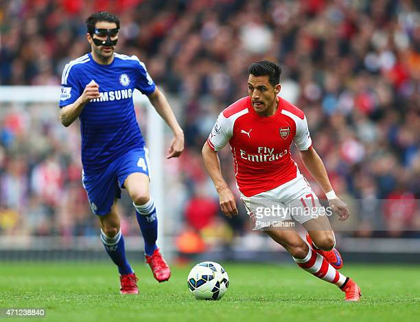Alexis Sanchez of Arsenal is chased by Cesc Fabregas of Chelsea during the Barclays Premier League match between Arsenal and Chelsea at Emirates...
