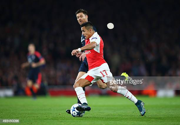 Alexis Sanchez of Arsenal is chased by Xabi Alonso of Bayern Munich during the UEFA Champions League Group F match between Arsenal FC and FC Bayern...