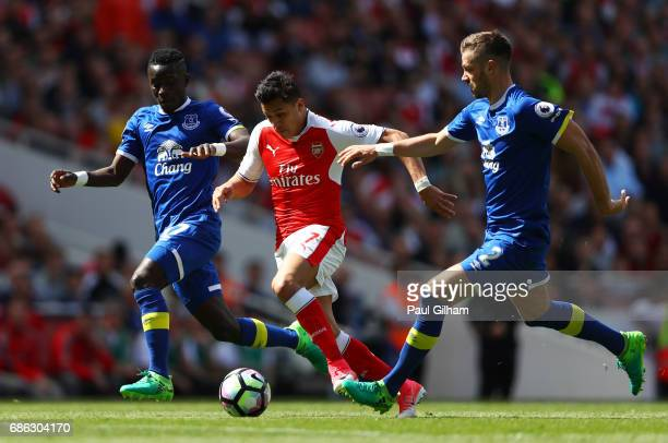 Alexis Sanchez of Arsenal is chased down by Morgan Schneiderlin of Everton during the Premier League match between Arsenal and Everton at Emirates...