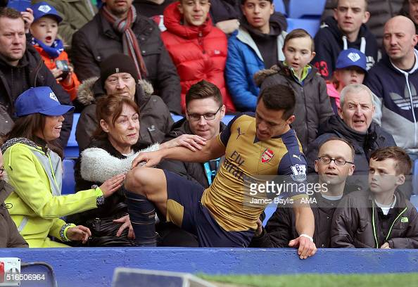 Alexis Sanchez of Arsenal is helped up by Everton supporters after he fell over the advertising boards during the Barclays Premier League match...
