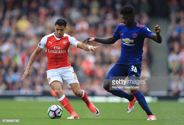 Alexis Sanchez of Arsenal is put under pressure from Axel Tuanzebe of Manchester United during the Premier League match between Arsenal and...