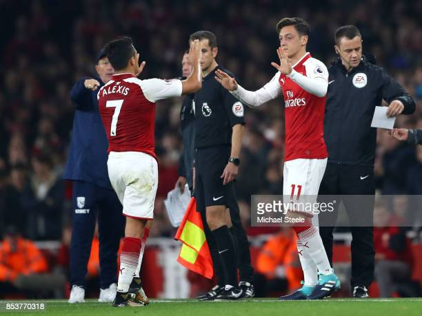 Alexis Sanchez of Arsenal is replaced by Mesut Ozil of Arsenal as he is substituted during the Premier League match between Arsenal and West Bromwich...